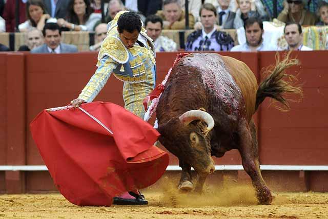 Alargándole la embestida al toro y estirando el brazo.