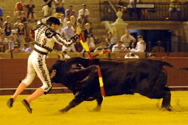 Levanta los brazos para adornarse pero el toro ya le ha cazado y empitonado. (FOTO: Sevilla Taurina)