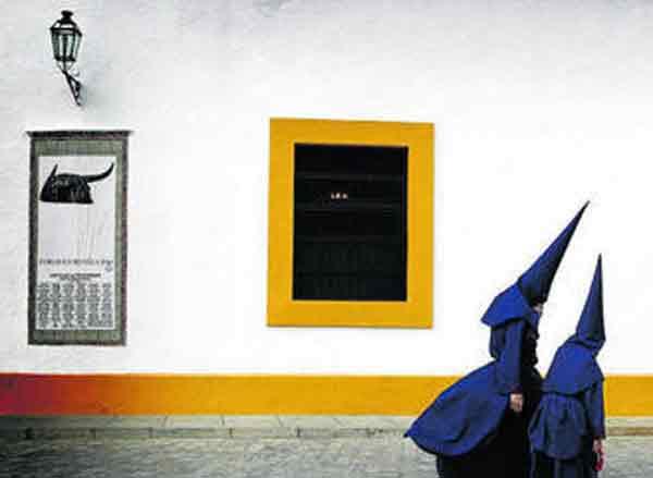 Dos nazarenos del Baratillo bajo el cartel de 2011.