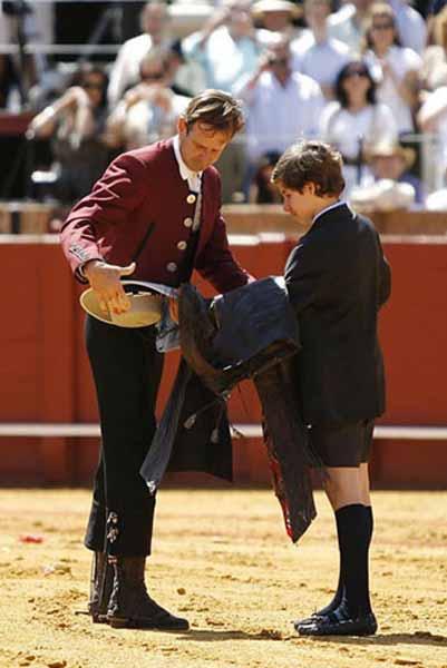 Antonio Domecq, tras su actuación esta mañana en la Maestranza, le entrega los zahones a su hijo en señal de retirada y herencia para una posible continuidad futura. (FOTOS: Arjona/lamaestranza.es)