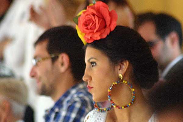 Los tedidos se llenan de mujeres guapas las tardes feriales. Una flamenca con dos flores 'bien plantá' en la cabeza. (FOTO: Javier Martínez)
