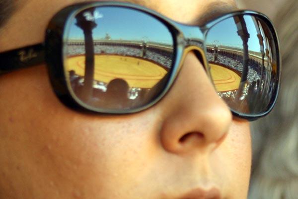 La plaza de la Maestranza reflejada en su integridad en las gafas de sol de una aficionada. (FOTO: Javier Martínez)