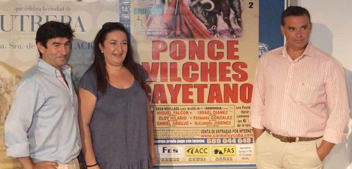 Los nuevos empresarios de Utrera y la delegada de Fiestas, junto al cartel. (FOTO: Matito)
