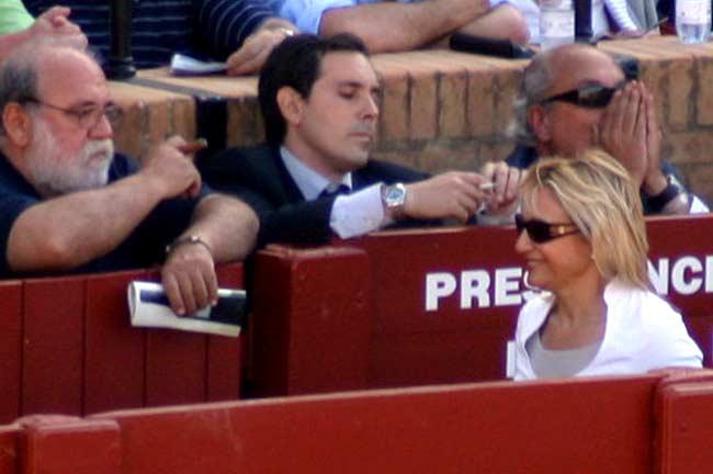 La delegada de la Junta, Carmen Tovar, pasa por delante del veterano veterimario Luis Vázquez, fumando un puro. (FOTO: Javier Martínez)