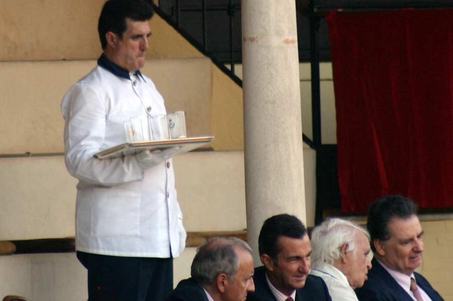 Un camarero retira los vasos de cristal en el palco particular de los maestrantes.