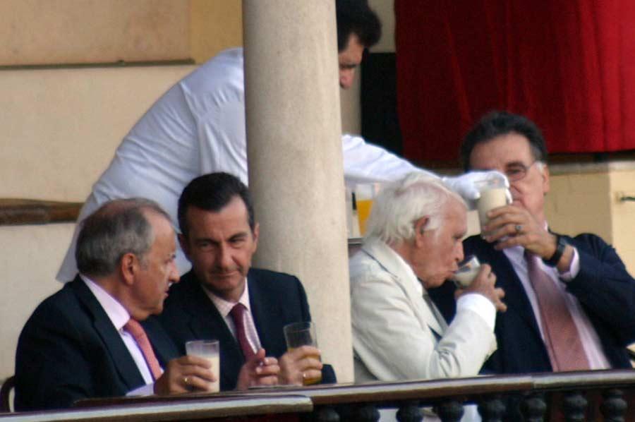 Miembros de la Real Maestranza consumiendo bebidas en vaso de cristal durante el festejo.