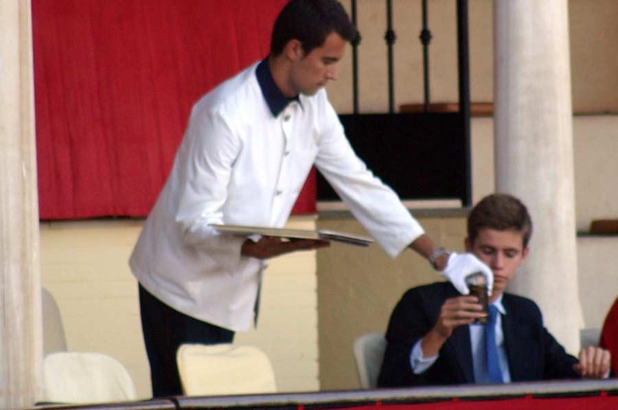 El camarero también sirve bebidas en vaso de cristal a familiares de los maestrantes.