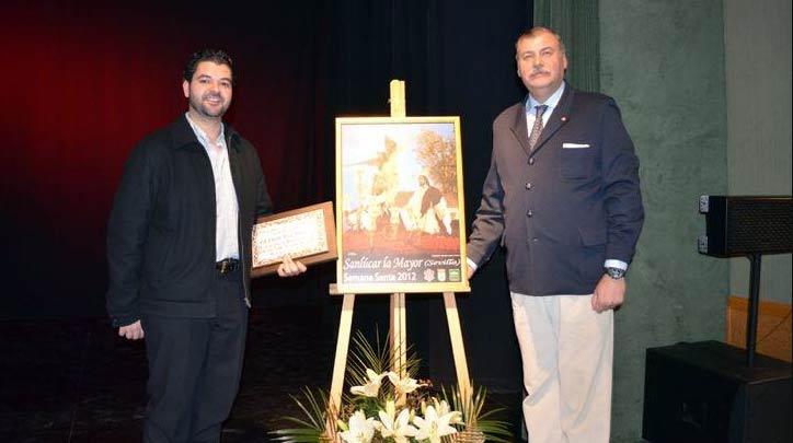 El fotógrafo taurino sevillano Eduardo López en la presentación del cartel de la Semana Santa de Sanlúcar la Mayor, con una fotografía de su obra.