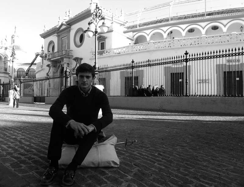 Una estampa que parece sacada de otra época: el aspirante a torero Paco Lama espera frente a la Maestranza con un hatillo que guarda espada y muleta. (FOTO: Javier Martínez)