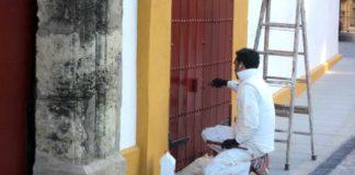 Un operario repasa de pintura una puerta de acceso a la plaza de Sevilla. (FOTO: Javier Martínez)