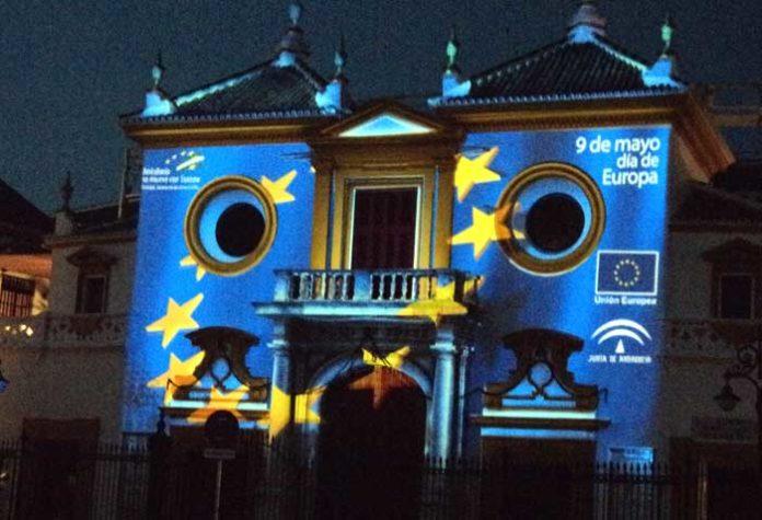 La bandera de Europa recorriendo la fachada de la Maestranza. (FOTO: Javier Martínez)