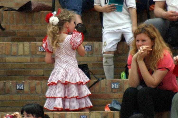 Y una joven aficionada que parece haber empalmado la Feria de Abril con la actual de Dos Hermanas.