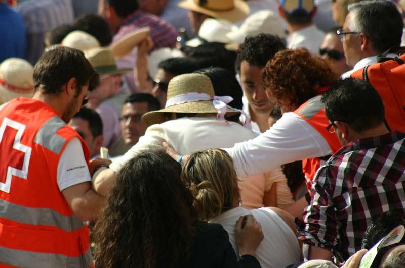 Miembros de la Cruz Roja evacuan a una señora mayor entre los asientos de los espectadores por la ausencia de escaleras.