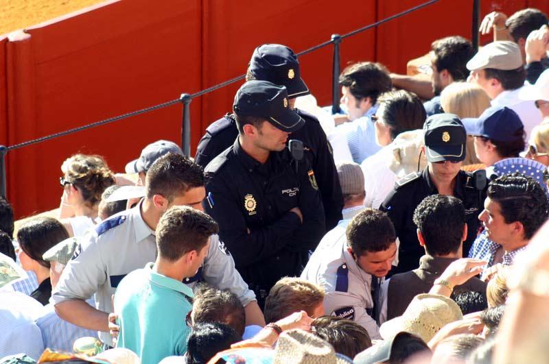 Tres policías y dos vigilantes de la empresa intentan parar a los espectadores que sólo quieren llegar al asiento que han pagado a alto precio.