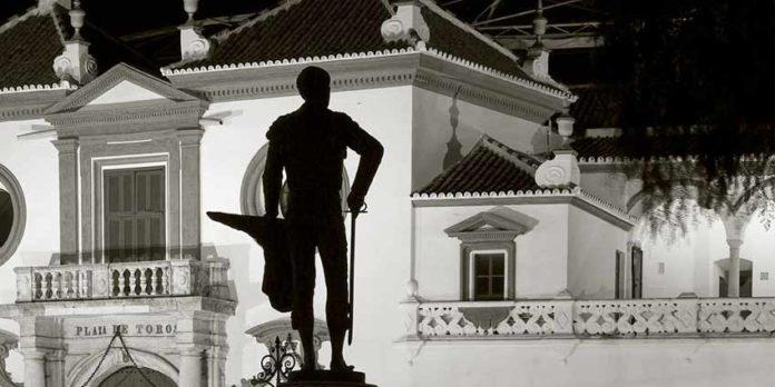 La silueta del monumento de Pepe Luis, con la muleta hecha un cartucho de pescado, se perfila frente a la Maestranza.