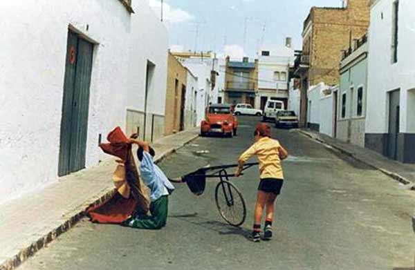 Morante niño jugando al toro en la puerta de su casa en La Puebla del Río mientras su primo y actual mozo de espadas, Juan Carlos Morante, le embiste con un pequeño carretón.