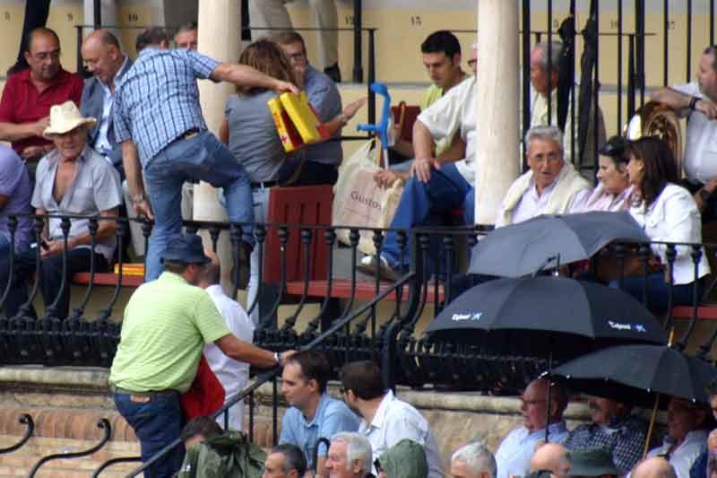 Varios aficionados se ponen a salvo de la lluvia subiendo a las gradas.