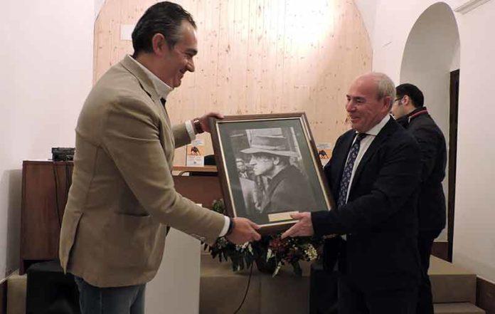 Roberto Rodríguez Gutiérrez recibe de manos del presidente del Círculo Cultural Taurino el primer premio del 'II Certamen literario taurino' de Osuna.